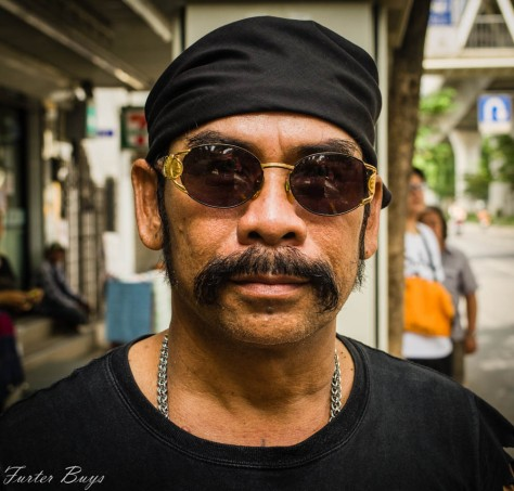 This guy was standing at a bus stop when I passed. I didn't have much time as  his bus was speedily approaching. I took two  shots and he said he had to go. He jumped on to the bus, waved goodbye and I never even got his name. Bangkok, 2013